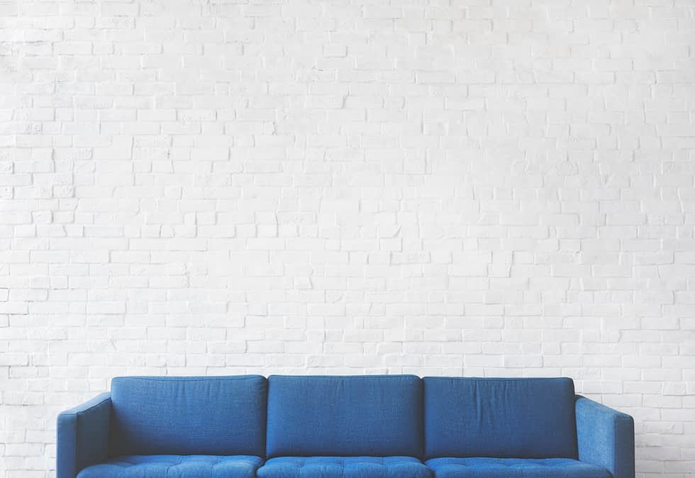 a blue couch and white wall